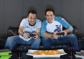 Zwei Maenner sitzen auf Sofa, spielen Videospiel