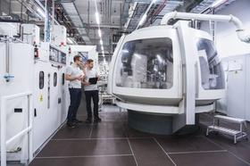 zwei junge Mitarbeiter kontrollieren Roboter in Fabrik
