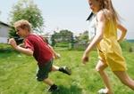 Zwei Kinder rennen auf Wiese