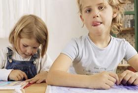 Zwei Maedchen sitzen am Tisch beim Malen