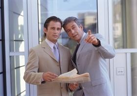 Zwei Manager stehen vor Gebaeudeeingang, unterhalten sich