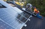 Zwei Männer in Schutzkleidung installieren Solarzellen auf Dach