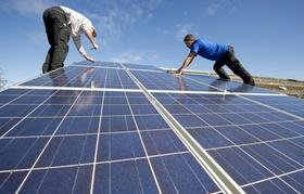 Zwei Männer installieren Solarzellen auf einem Dach