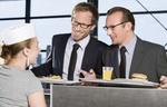 Zwei Männer nehmen lachend ihr Essen auf Tablets entgegen