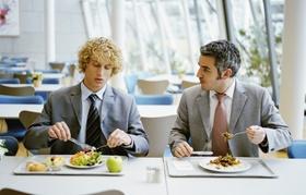 Zwei Männer sitzen in Kantine und unterhalten sich
