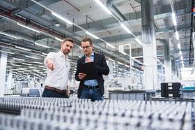 Zwei Männer stehen an Maschine