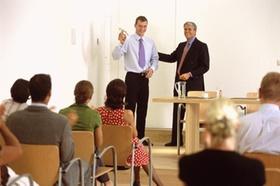 Zwei Männer stehen im Seminar vor Teilnehmern
