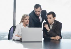 Zwei Männer und eine Frau im Büro an Laptop
