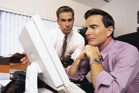 Zwei Männer vor dem Computer, einer sitzt, einer steht