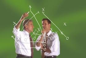 Zwei Männer zeichnen Linien vor grüner Wand