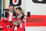 Zwei Rettungssanitäter stehen vor einem Rettungswagen