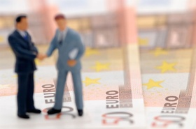 two figures of business men standing upon bank notes